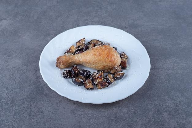 Udko z kurczaka z grilla i bakłażan na białym talerzu.
