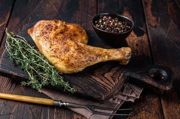 Udko z kurczaka z grilla na drewnianej desce. ciemne drewniane tło. widok z góry.