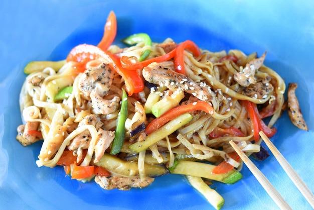 Udon z kurczakiem i warzywami w sosie sojowym na talerzu
