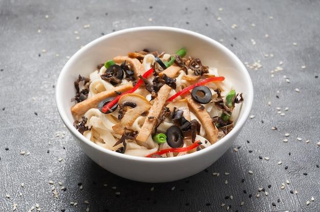 Udon z kurczakiem, warzywami i pieczarkami. kuchnia japońska