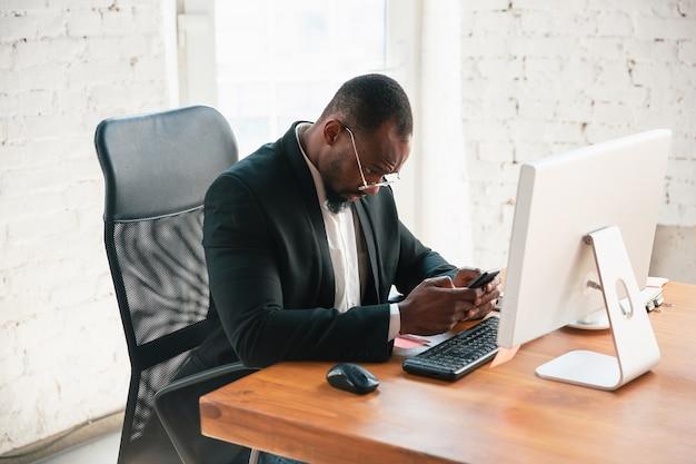 Udostępnianie online. afro-przedsiębiorca, biznesmen pracujący skoncentrowany w biurze. wygląda serio i zajęty, ma na sobie klasyczny garnitur, marynarkę. pojęcie pracy, finansów, biznesu, sukcesu, przywództwa.