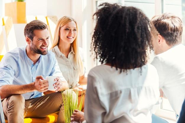 Udostępnianie wiadomości biurowych. grupa szczęśliwych młodych ludzi rozmawiających o czymś siedząc w strefie odpoczynku w biurze