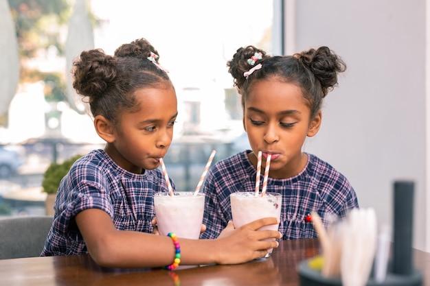 Udostępnij koktajl. urocze, poczciwe siostry w kwadratowych sukienkach dzielą się ze sobą mlecznymi koktajlami