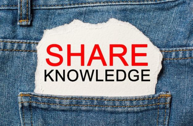 Udostępnij wiedzę na rozdartym tle papieru na koncepcji dżinsów i finansów