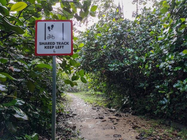 Udostępniony ślad trzymaj w lewo. znak wspólnej ścieżki pieszych i rowerzystów, singapur.
