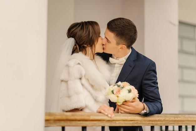 Uduchowione zdjęcie nowożeńców przytulających się i całujących. fotografia ślubna stylowej pary młodej.