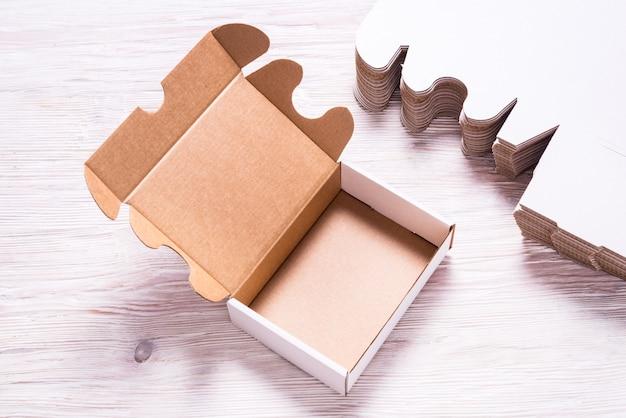 Udział kwadratowy karton boksuje na drewnianym tle, cutted