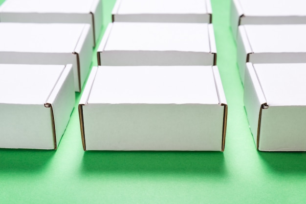 Udział kwadratowy karton boksuje na zielonym tle