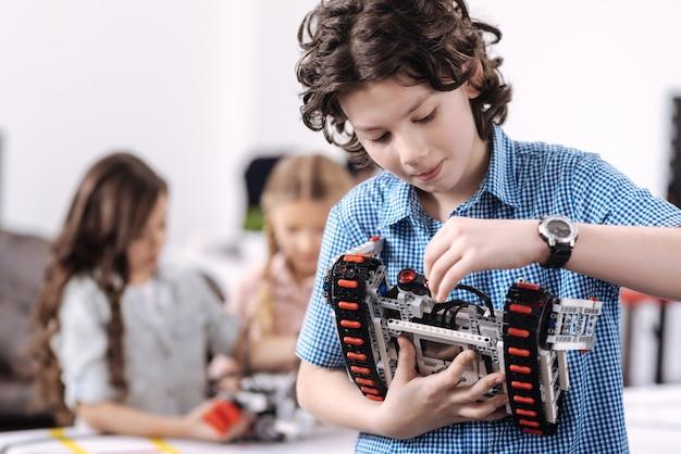 Udział w postępie nauki. zachwycony, wesoły skoncentrowany chłopiec stojący przy szkole i trzymający robota podczas jego naprawy oraz kolegów z klasy pracujących nad projektem