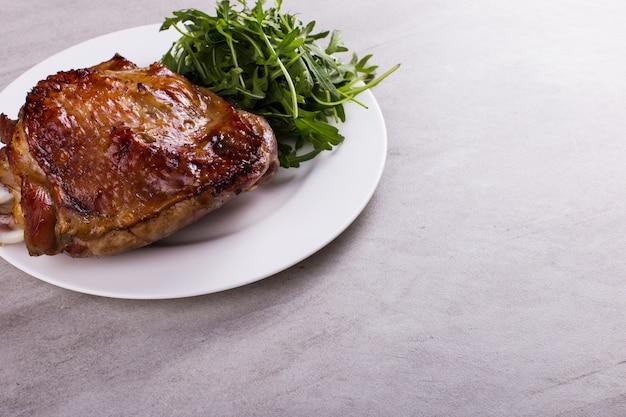 Udziec z indyka zapiekany w piekarniku z przyprawami na białym talerzu na stole. zdrowe jedzenie. obiad dziękczynny.