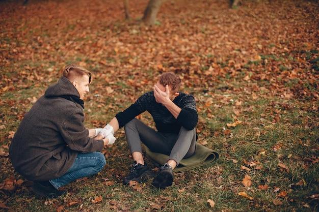Udzielanie pierwszej pomocy w parku. mężczyzna zabandażował ranne ramię. facet pomaga przyjacielowi.