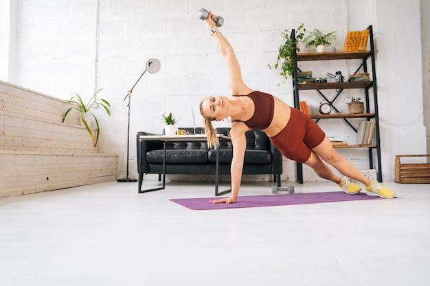 Ufa, rosja - 15 maja 2020. wysportowana młoda kobieta o idealnym atletycznym ciele, ubrana w odzież sportową, wykonująca boczną deskę z hantlami podczas treningu. pojęcie zdrowego stylu życia