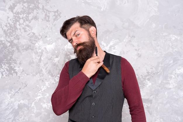 Ufam tylko sobie. brodaty mężczyzna z brzytwą. brutalny mężczyzna z brodą trzyma brzytwę do golenia. hipster klasyczny styl brody do golenia. gładkie golenie. fryzjer z rocznika narzędzia fryzjerskiego. fryzjer z brzytwą.