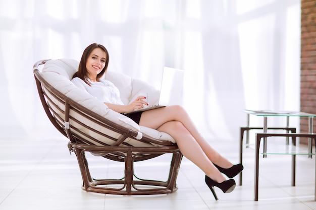 Ufna biznesowa kobieta z dokumentami siedzi wokół wygodnego krzesła