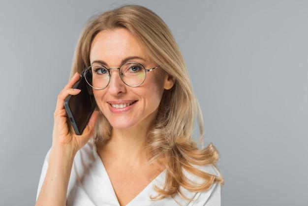 Ufna blondynki młoda kobieta opowiada na mądrze telefonie przeciw popielatemu tłu