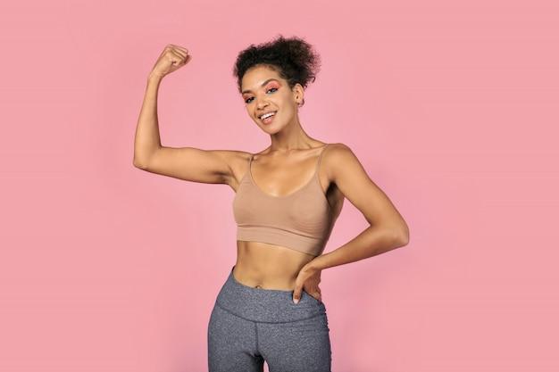 Ufna czarna kobieta pokazująca muskulaturę i siłę. afrykańska kobieta w stylowej odzieży sportowej pozowanie na różowym tle.