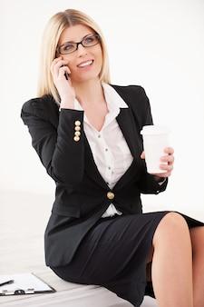 Ufna dojrzała bizneswoman. piękna dojrzała kobieta rozmawia przez telefon komórkowy i trzyma filiżankę kawy