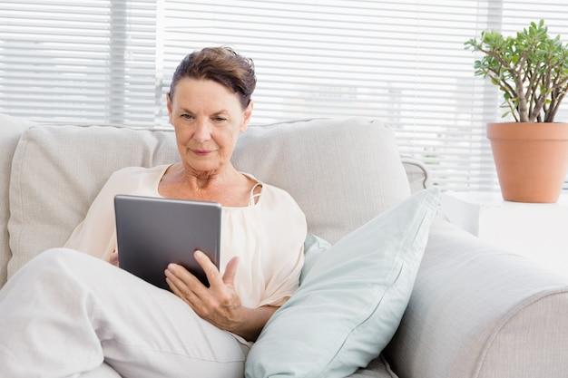 Ufna dojrzała kobieta używa cyfrową pastylkę
