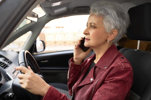 Ufna dojrzała kobieta w stylowej kurtce prowadzącej samochód po ulicach miasta i jednocześnie mówiąca na telefonie komórkowym