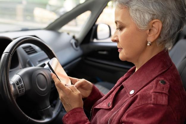 Ufna, dojrzała kobieta w stylowej kurtce rozmawia ze swoim smartfonem w samochodzie