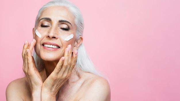 Ufna dojrzała kobieta z produktem do pielęgnacji skóry