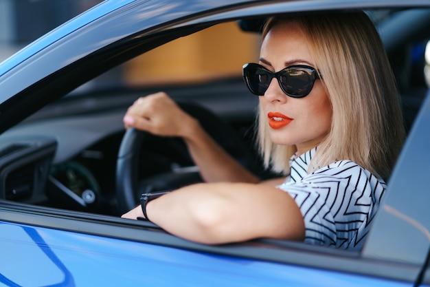 Ufna i piękna kobieta w okularach przeciwsłonecznych. widok z tyłu atrakcyjnej młodej kobiety w codziennym noszeniu prowadzenia samochodu