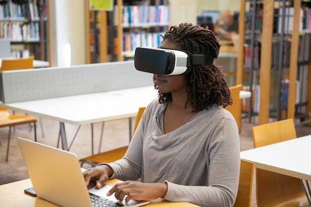 Ufna kobieta pisać na maszynie na laptopie podczas gdy siedzący w vr słuchawki