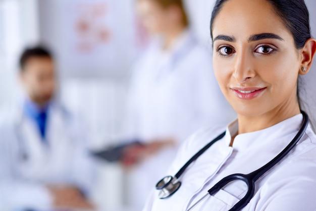 Ufna kobiety lekarka przed drużyną, patrzejący kamerę ono uśmiecha się, wielorasowa drużyna z arabską kobiety lekarką