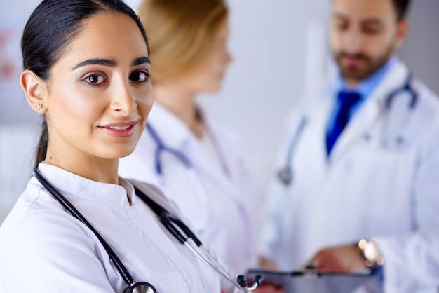 Ufna kobiety lekarka przed drużyną, patrzeje uśmiechniętą, wielorasową drużynę z arabską kobiety lekarką