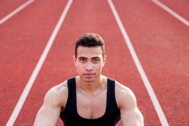 Ufna mięśniowa sport osoba patrzeje kamerę na czerwonym biegowym śladzie
