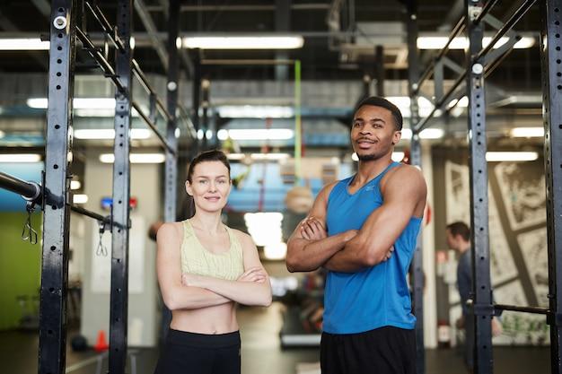 Ufna mieszanej rasy para pozuje w gym