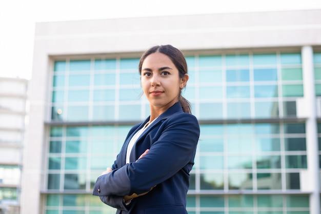 Ufna młoda bizneswoman pozycja z krzyżować rękami
