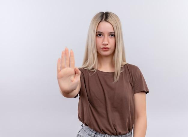 Ufna młoda blondynka wyciągająca rękę, gestykulując zatrzymaj się na odosobnionej białej przestrzeni z kopią miejsca