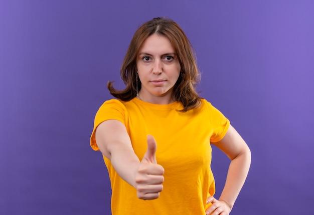Ufna młoda kobieta dorywczo pokazująca kciuk do góry na odosobnionej fioletowej przestrzeni z miejsca na kopię