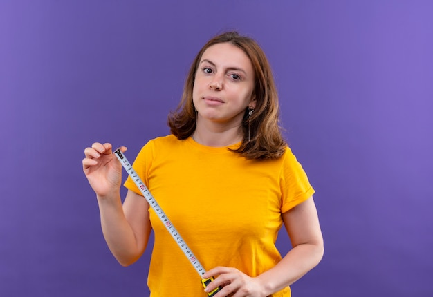Ufna młoda kobieta dorywczo trzymająca miernik taśmy na odosobnionej fioletowej przestrzeni z miejsca na kopię