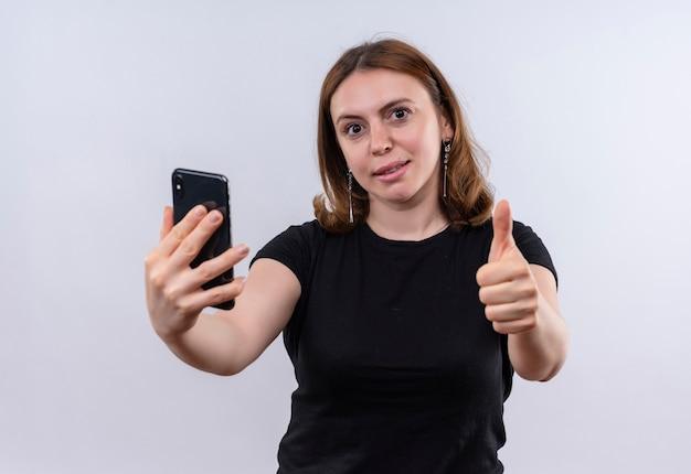 Ufna młoda kobieta dorywczo wyciągając telefon komórkowy i pokazując kciuk do góry na odosobnionej białej przestrzeni