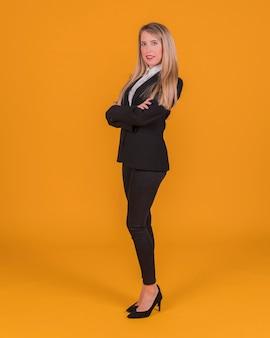 Ufna młoda kobieta stoi na pomarańczowym tle