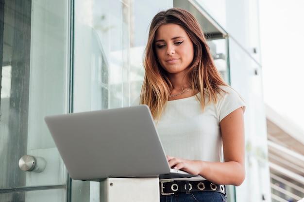 Ufna młoda kobieta wyszukuje laptop