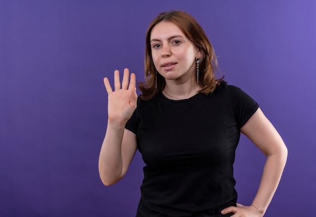 Ufna młoda przypadkowa kobieta gestykulująca cześć ręką na talii na odosobnionej fioletowej przestrzeni z kopią miejsca