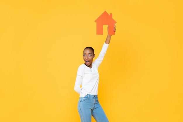 Ufna uśmiechnięta amerykanin afrykańskiego pochodzenia kobieta trzyma up domową ikonę wycinającą w kolor żółty odizolowywającej ścianie