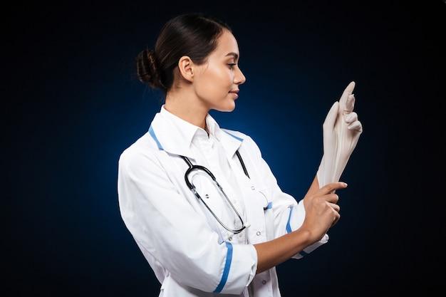 Ufna uśmiechnięta lekarka jest ubranym medyczne rękawiczki odizolowywać
