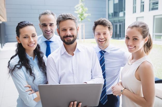 Ufni biznesmeni stoi na zewnątrz budynku biurowego z laptopem