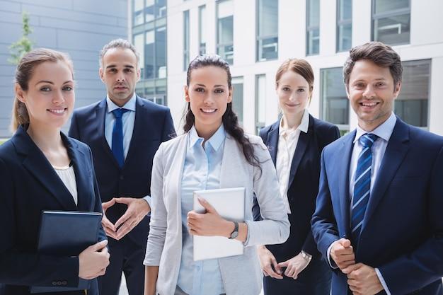 Ufni biznesmeni stoi na zewnątrz budynku biurowego
