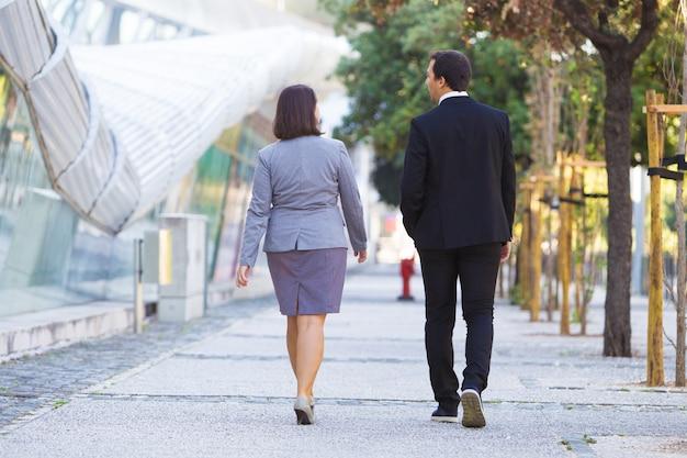 Ufni biznesowi koledzy w formalnych kostiumach iść biuro
