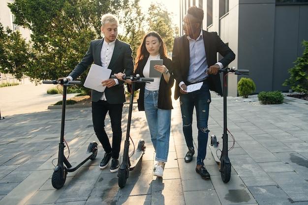 Ufni, szczęśliwi, wielorasowi koledzy z biura omawiający projekt biznesowy idą w pobliżu budynku biurowego ze skuterem elektrycznym