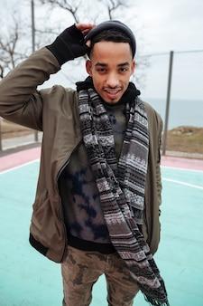 Ufny afrykański mężczyzna stoi outdoors i ono uśmiecha się w jesieni