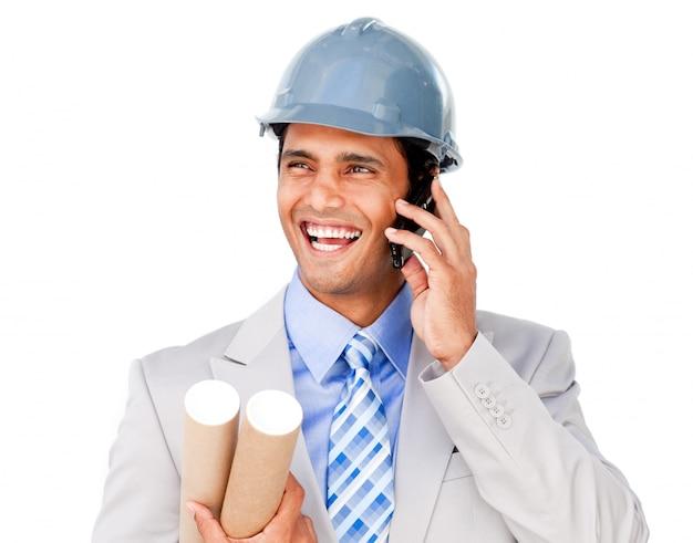 Ufny biznesmen jest ubranym hardhat na telefonie