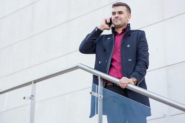 Ufny biznesmen opowiada na telefonie komórkowym
