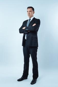Ufny biznesmen. poważny miły przystojny mężczyzna stojący na niebieskim tle i krzyżujący ramiona, pokazując jednocześnie swoją pewność siebie