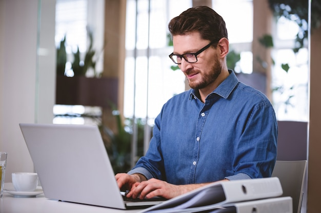 Ufny biznesmen pracuje na laptopie przy kreatywnie biurem